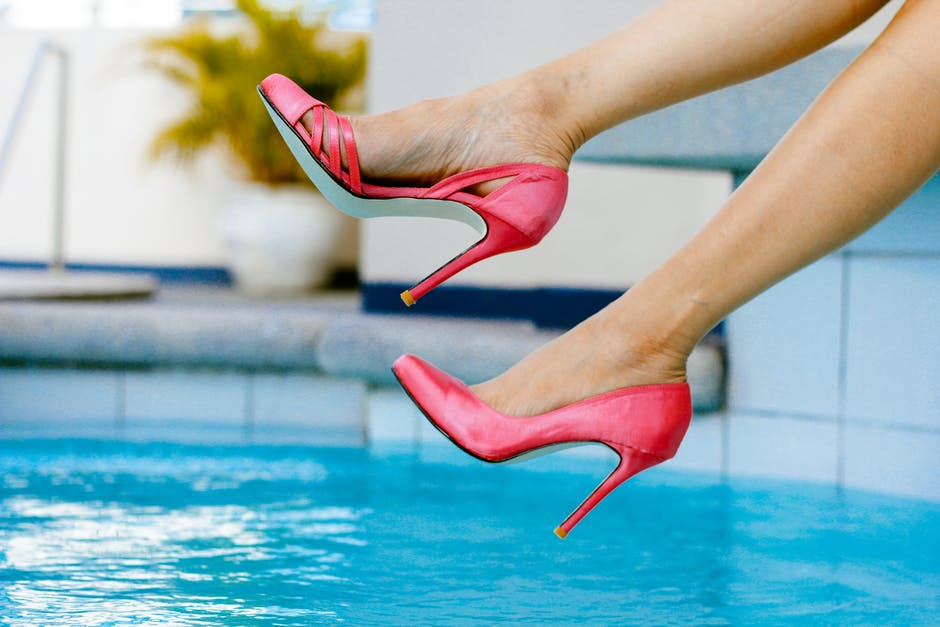 Woman Swinging Her Foot Above Pool Water