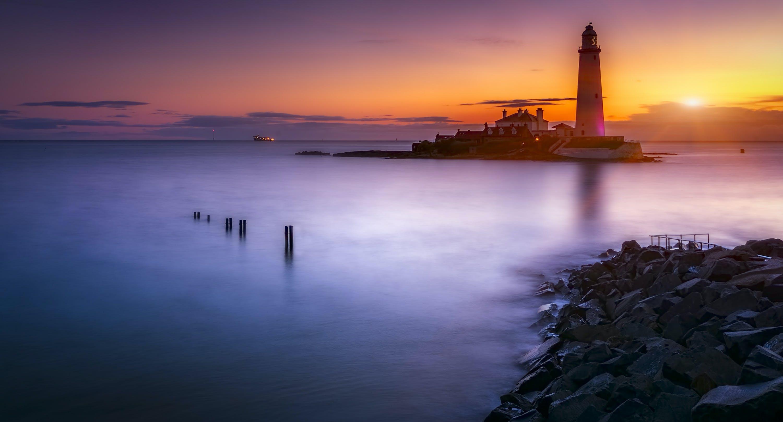 Lighthouse On Island Under Orange Sunset