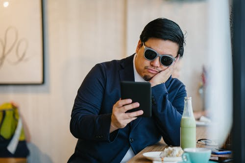Man Wearing Grey Sunglasses Holding Black Tablet