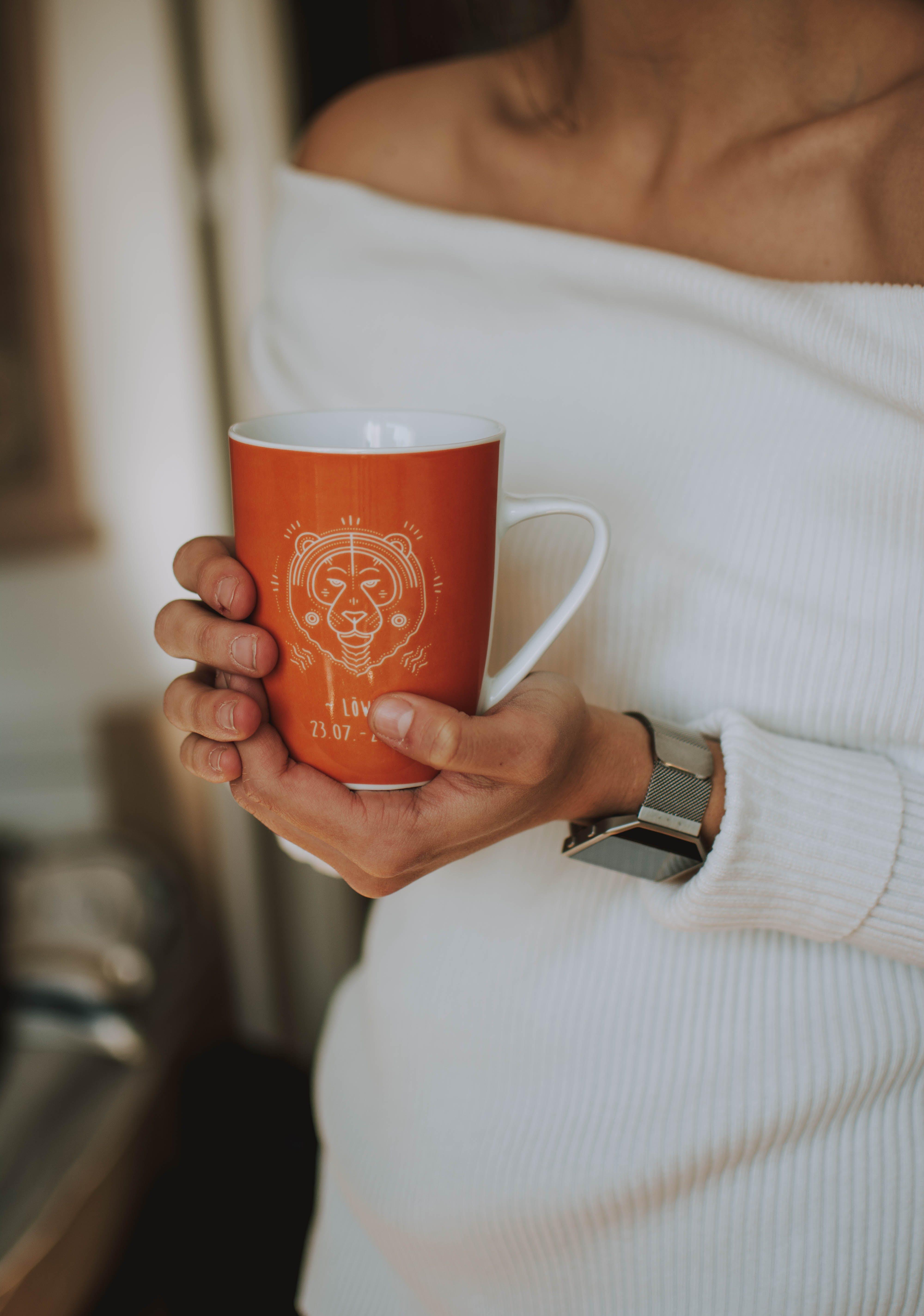 Woman Holding White and Orange Ceramic Mug