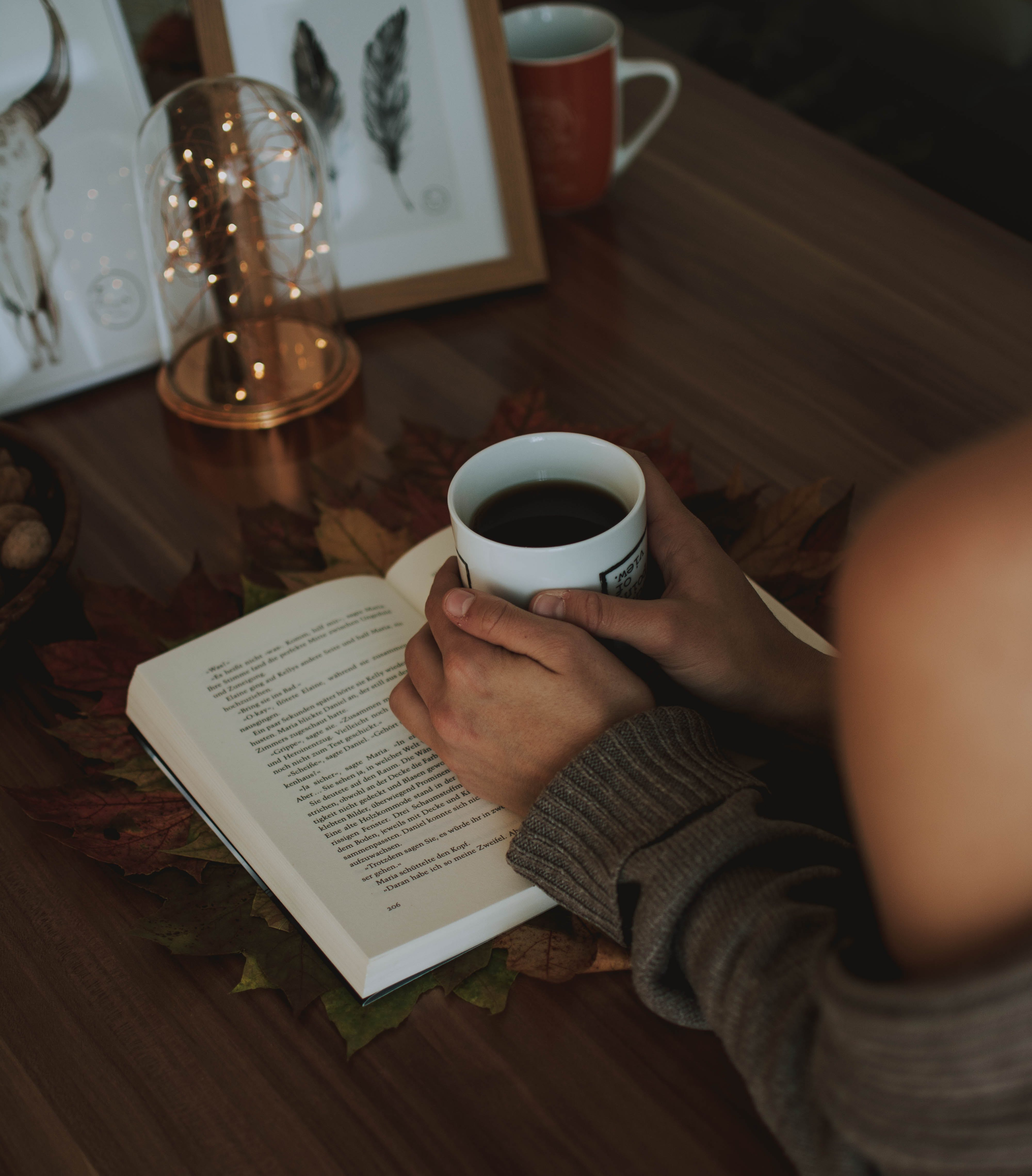 Girl Holding Mug of Coffee Above Opened Book on Brown Wooden Table