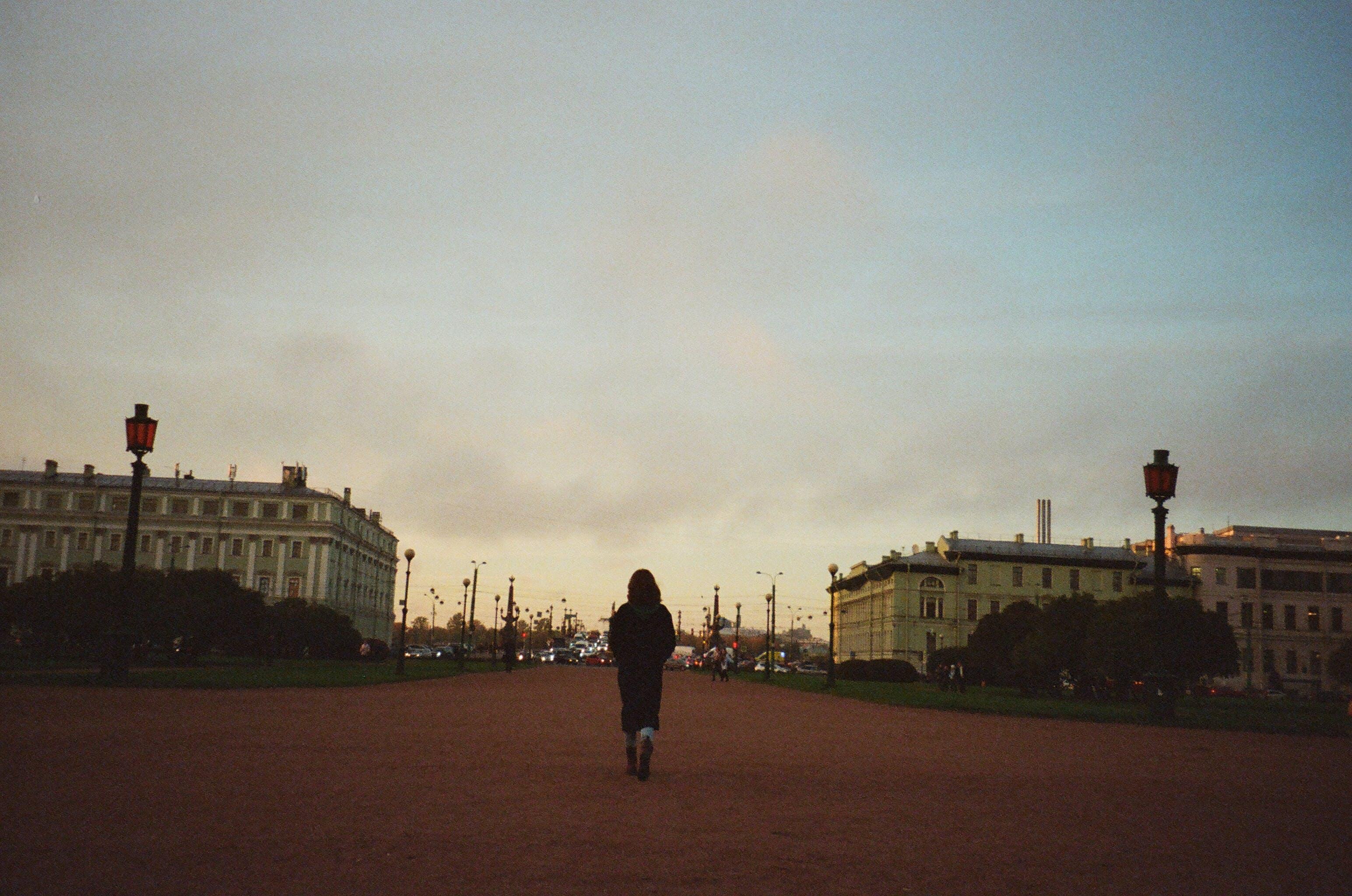Woman Walking Towards City