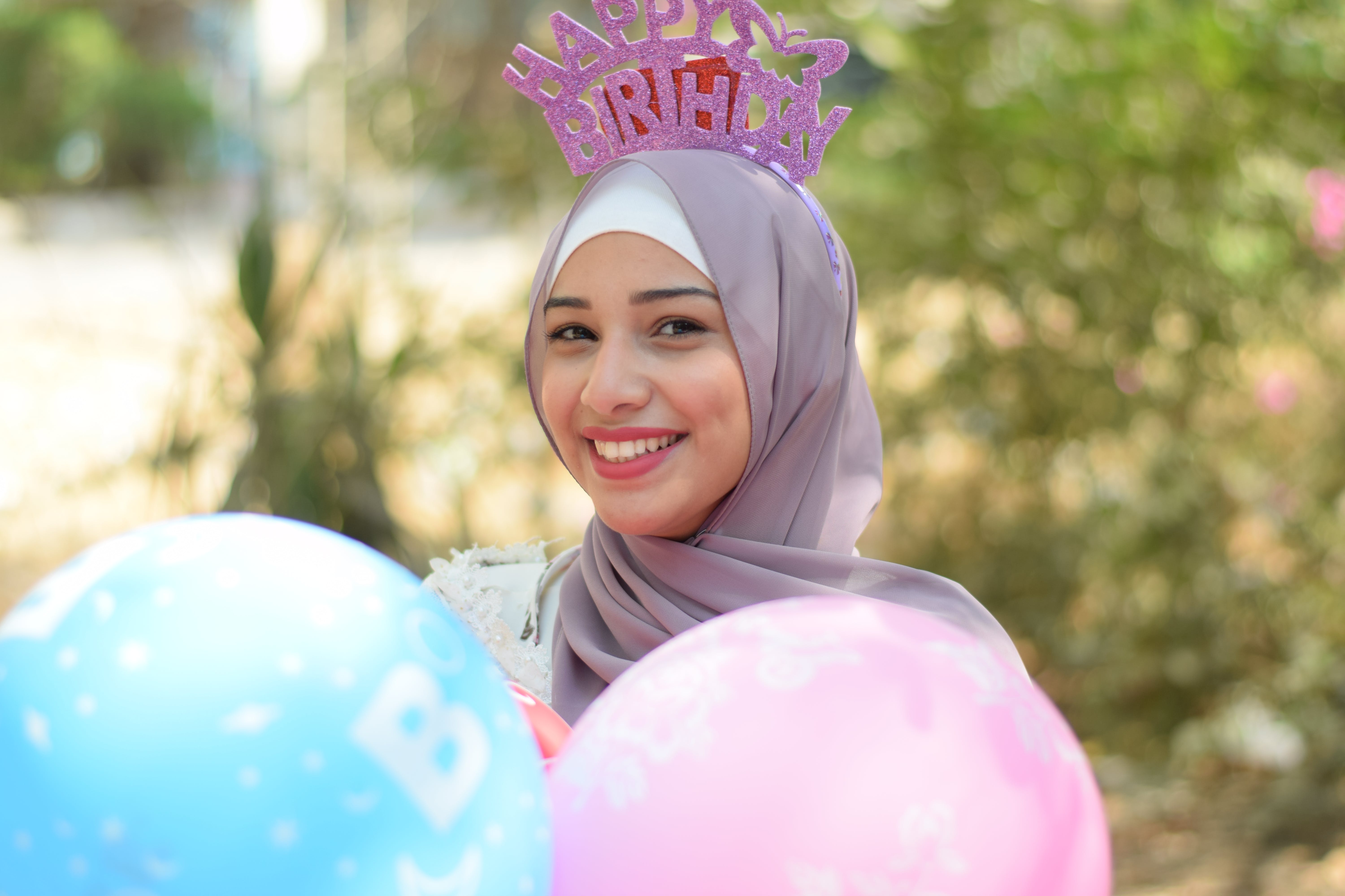 Smiling Woman Wearing Grey Hijab Headscarf and Holding Pink and Blue Balloons