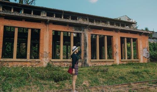 Femme Debout Près Du Bâtiment En Brique