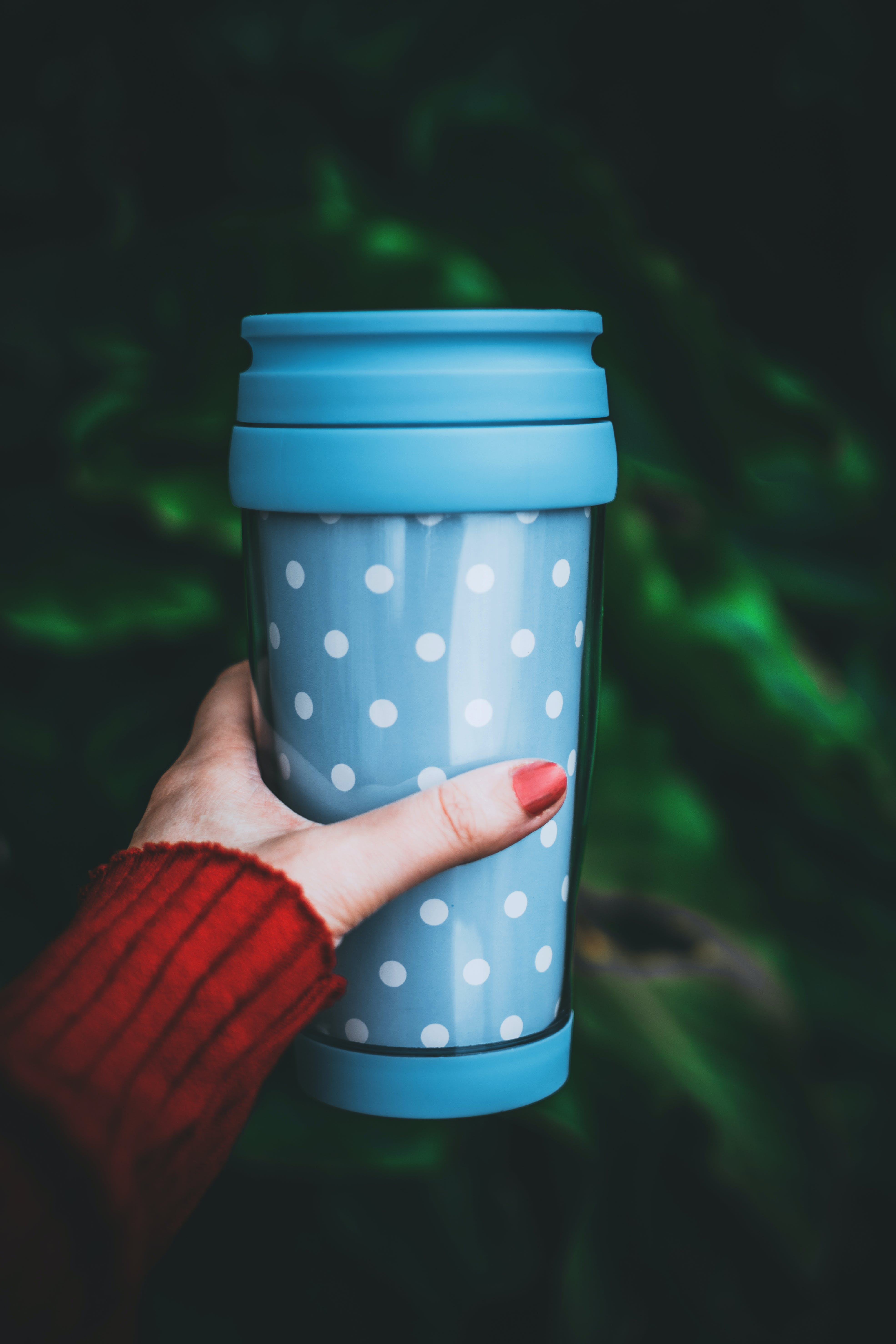 Person Holding Teal and White Polka-dot Tumbler
