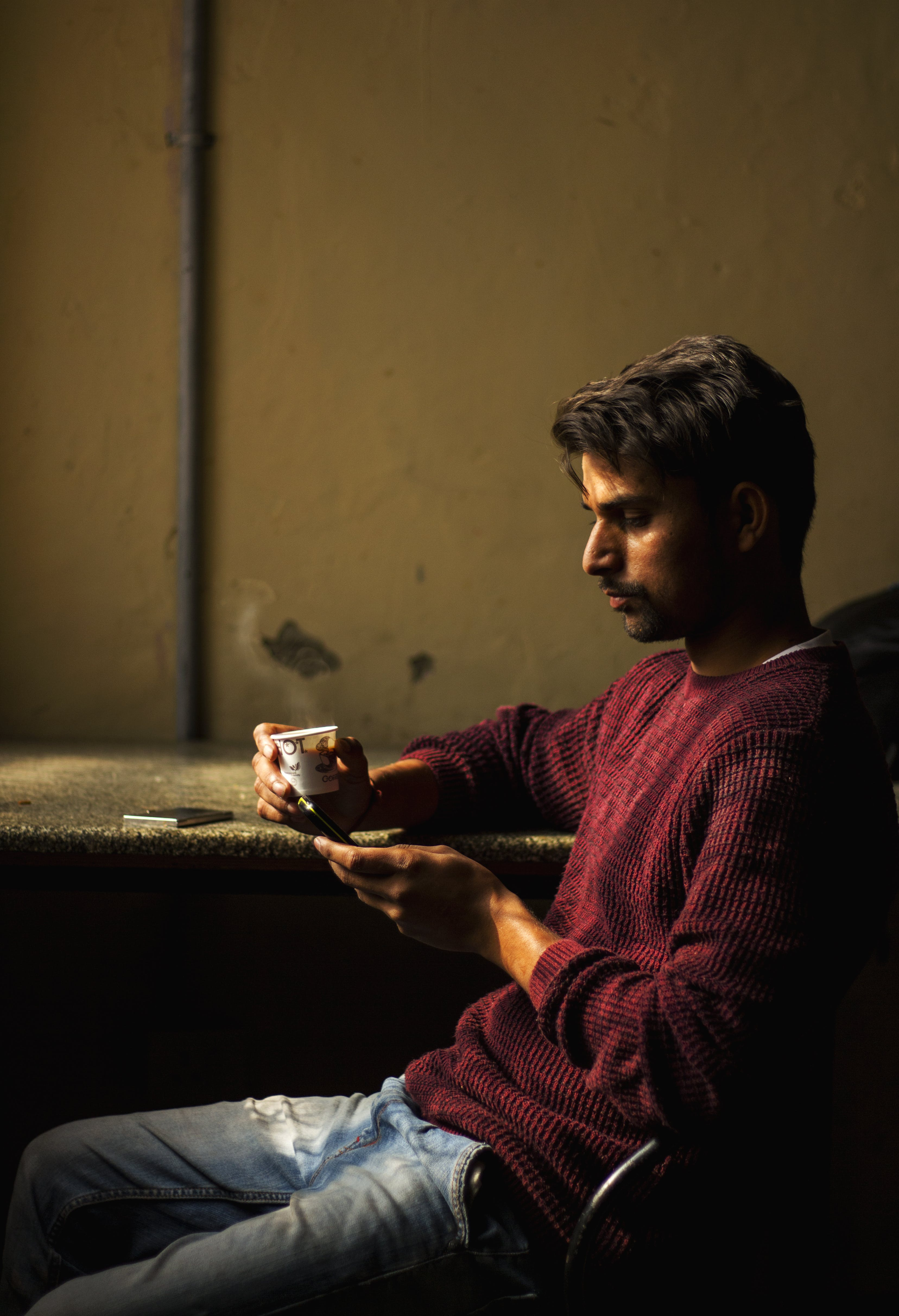 Man Wearing Red Sweater Sitting at Brown Table Holding White Cup