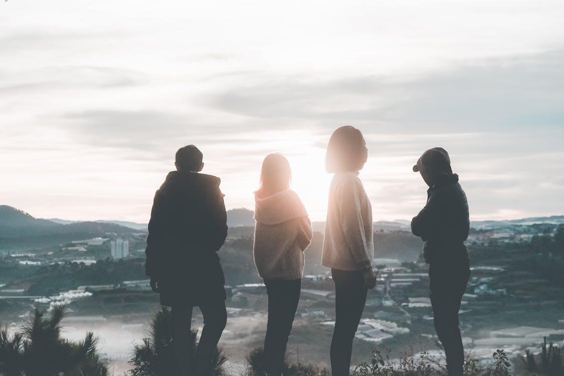 Four People Standing on Top of Hill during Sunset