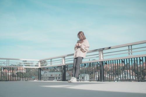 Foto profissional grátis de abrigo, céu, de pé, garota
