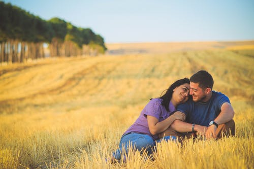 Man and Woman Sitting on Grass Field