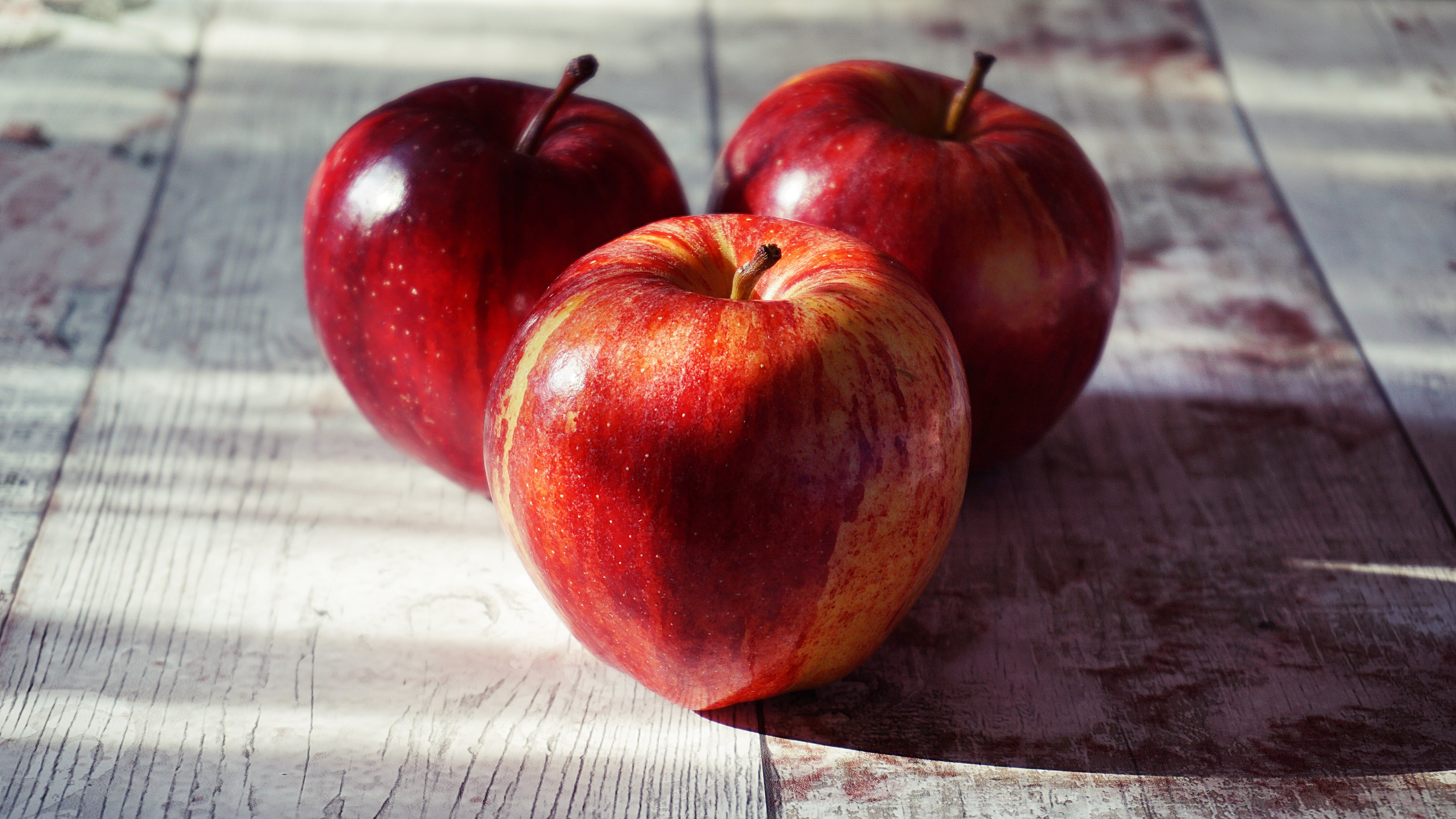 Three Red Apples on Brown Wooden Surface