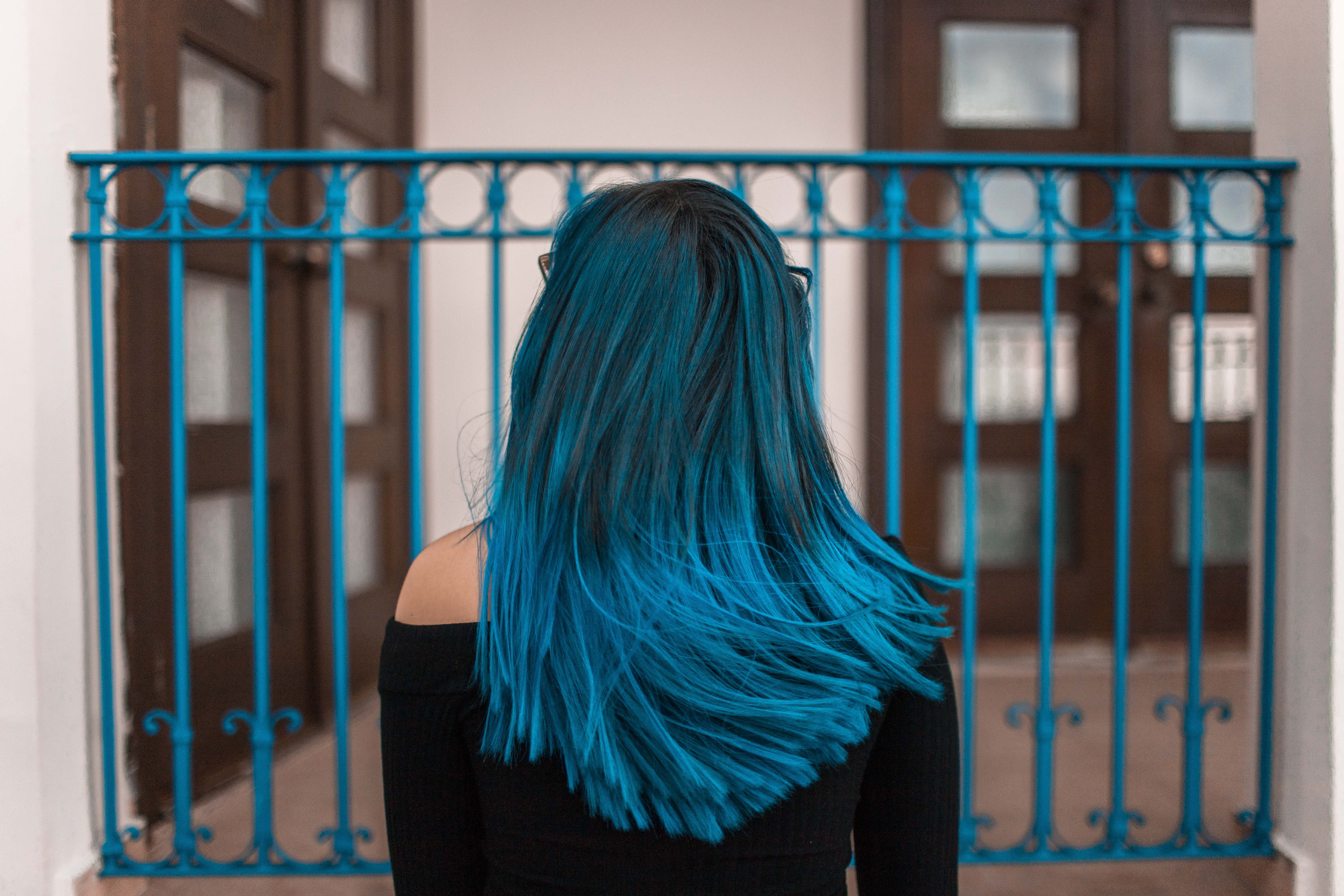 Blue Haired Woman Facing Metal Fence