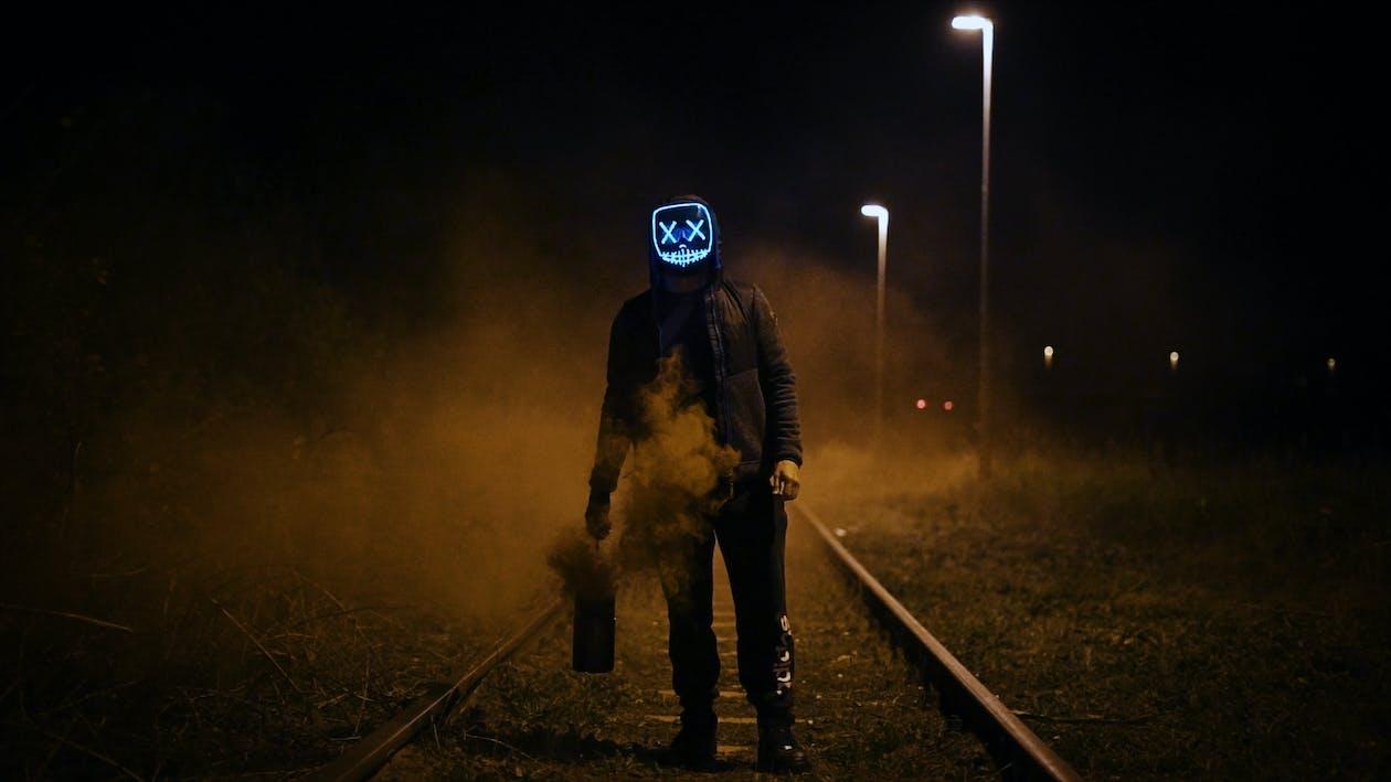 Man Wearing Black Jacket Standing On Railroad