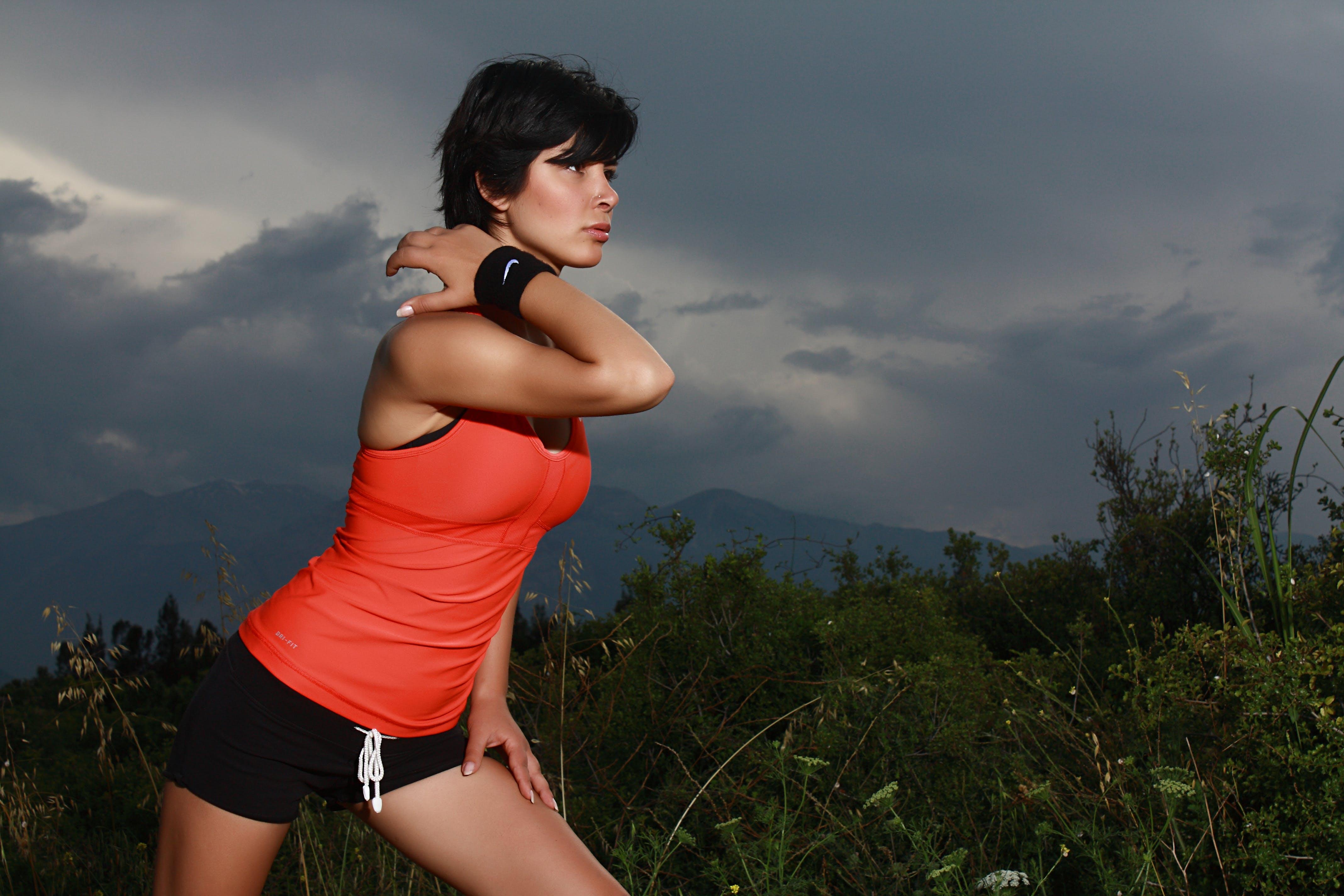 Woman Stretching Her Body Beside Green Grass