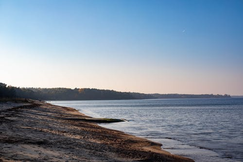 Wild sandy beach and calm sea during sundown