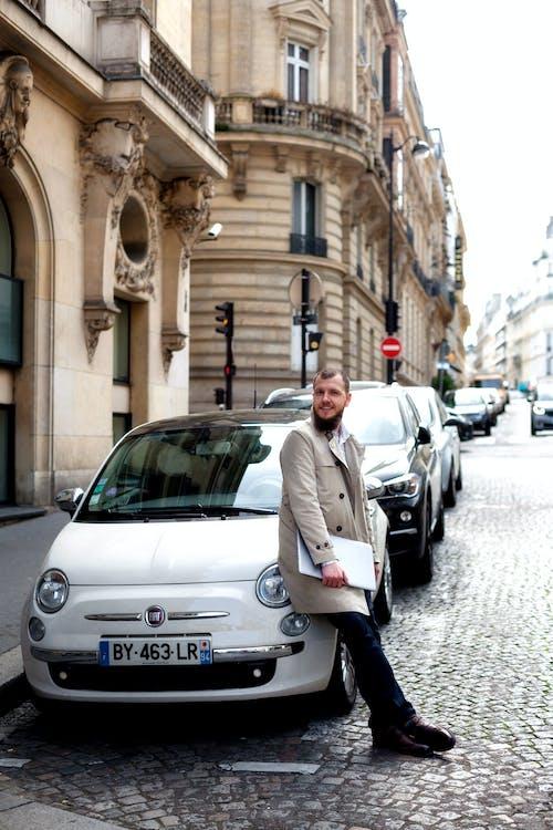 Man in White Coat Standing Beside White Car