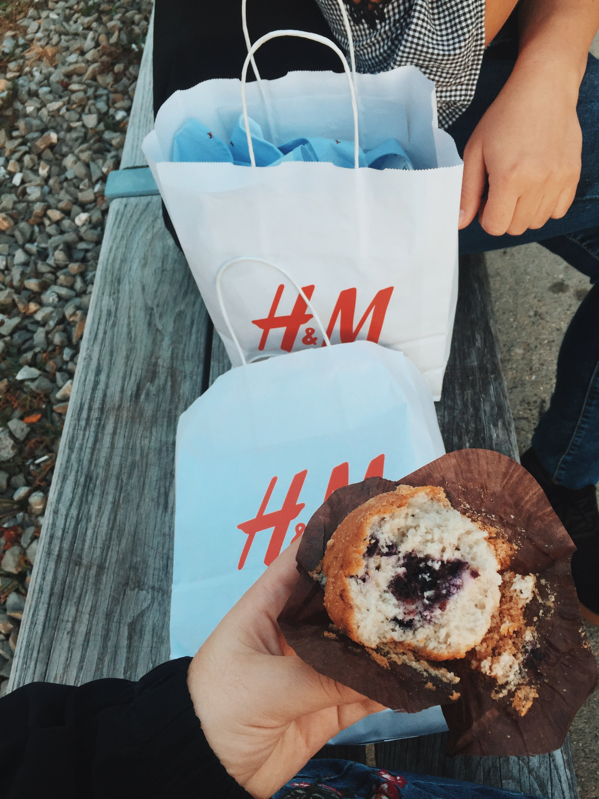 Person Holding Muffins Near the Two White H&m's Paper Bags