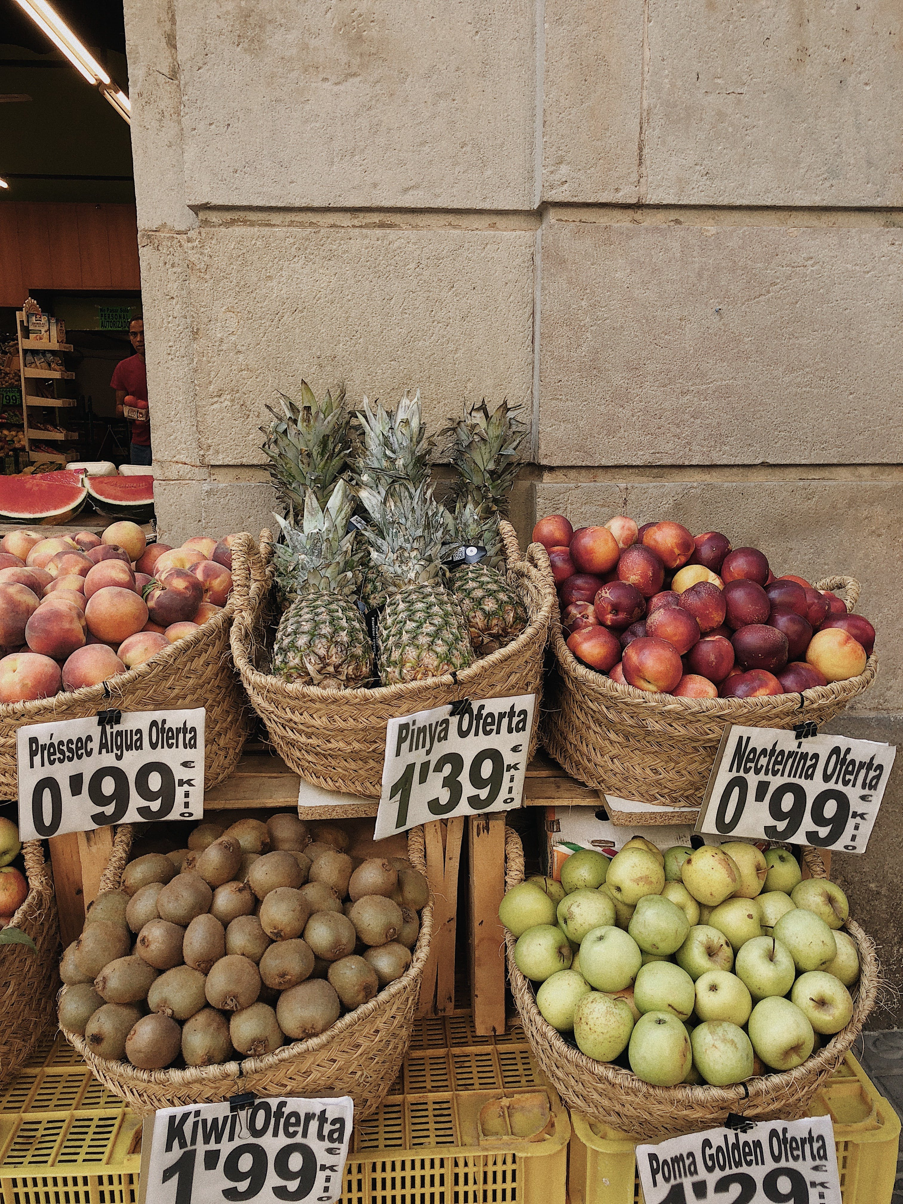 Baskets of Fruits Near Brown Concrete Wall