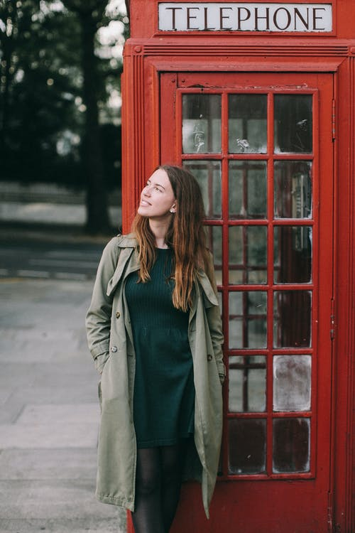 Photograph of a Woman Standing in Front of a Telephone Booth