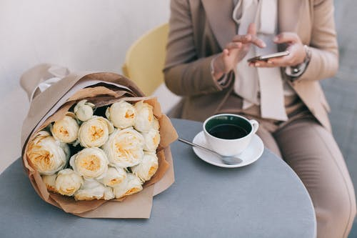 Bouquet of White Roses Beside Cup of Tea