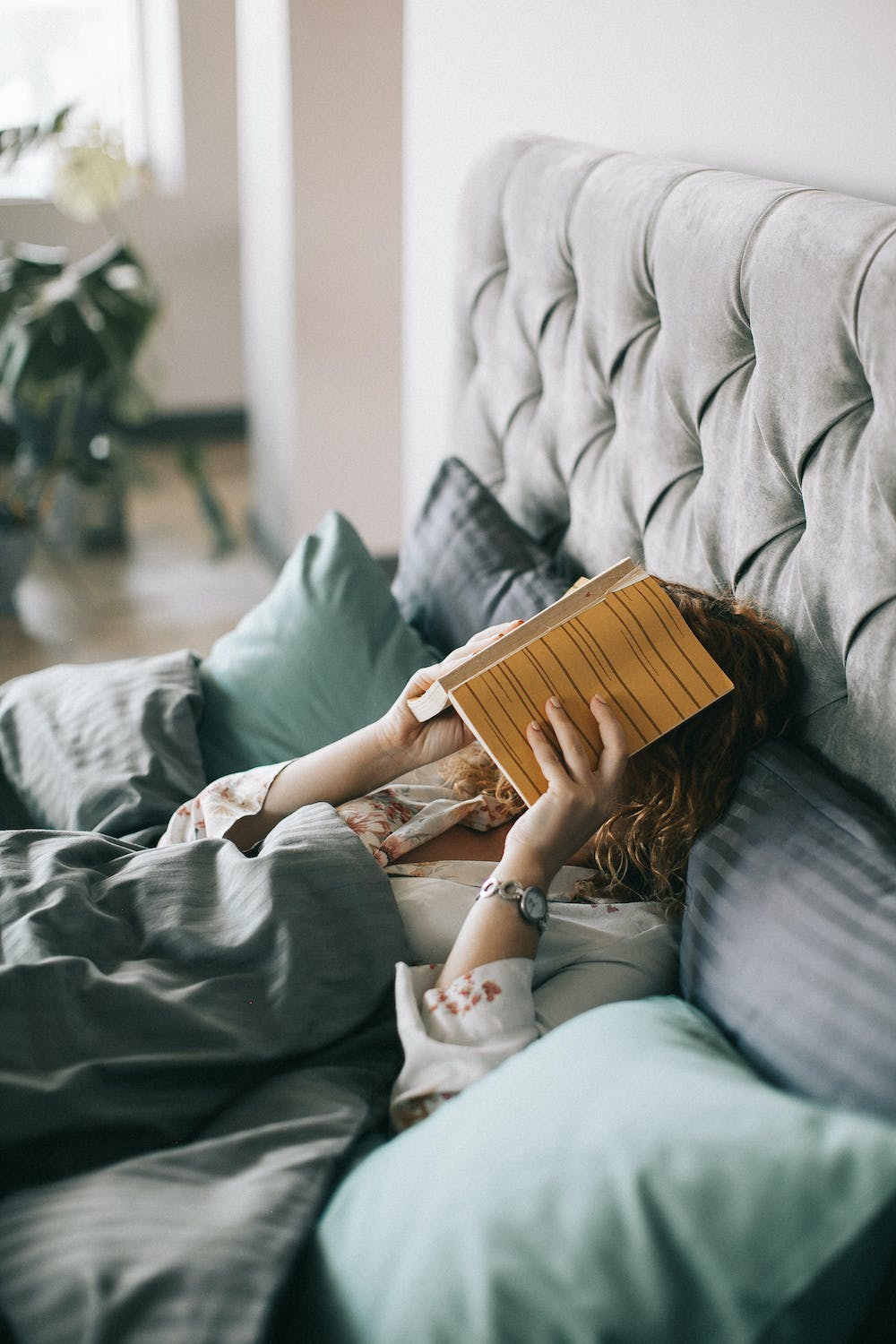 A woman reading book in bed. | Photo: Pexels