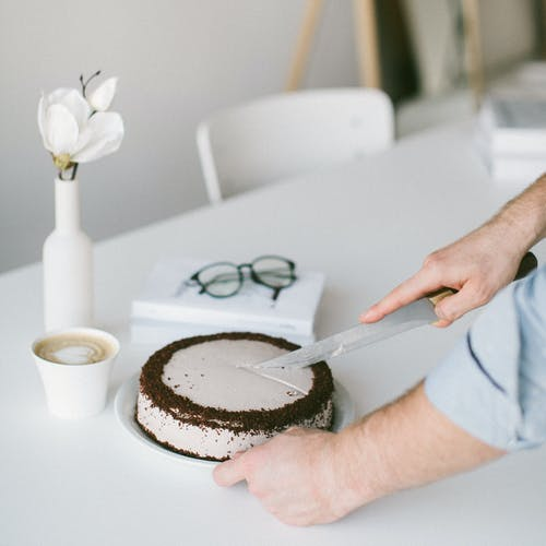 Person Slicing Cake on Table