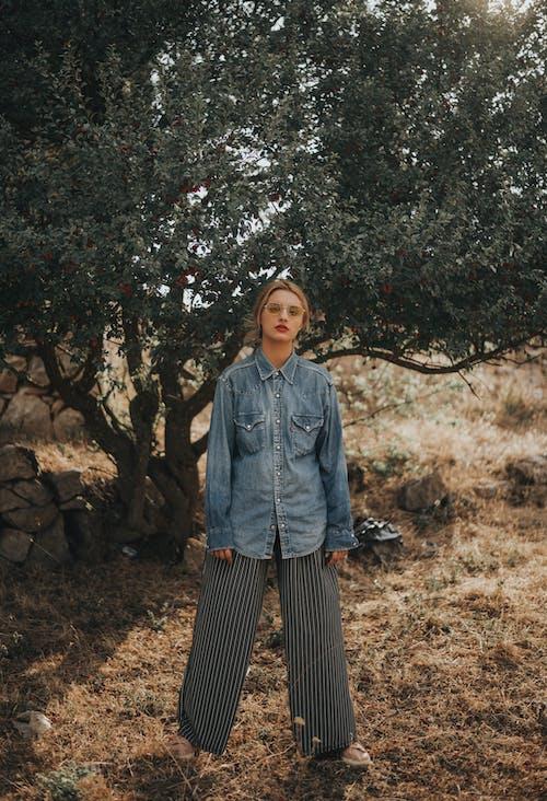 Бесплатное стоковое фото с брюки, дерево, джинсовая куртка, женщина