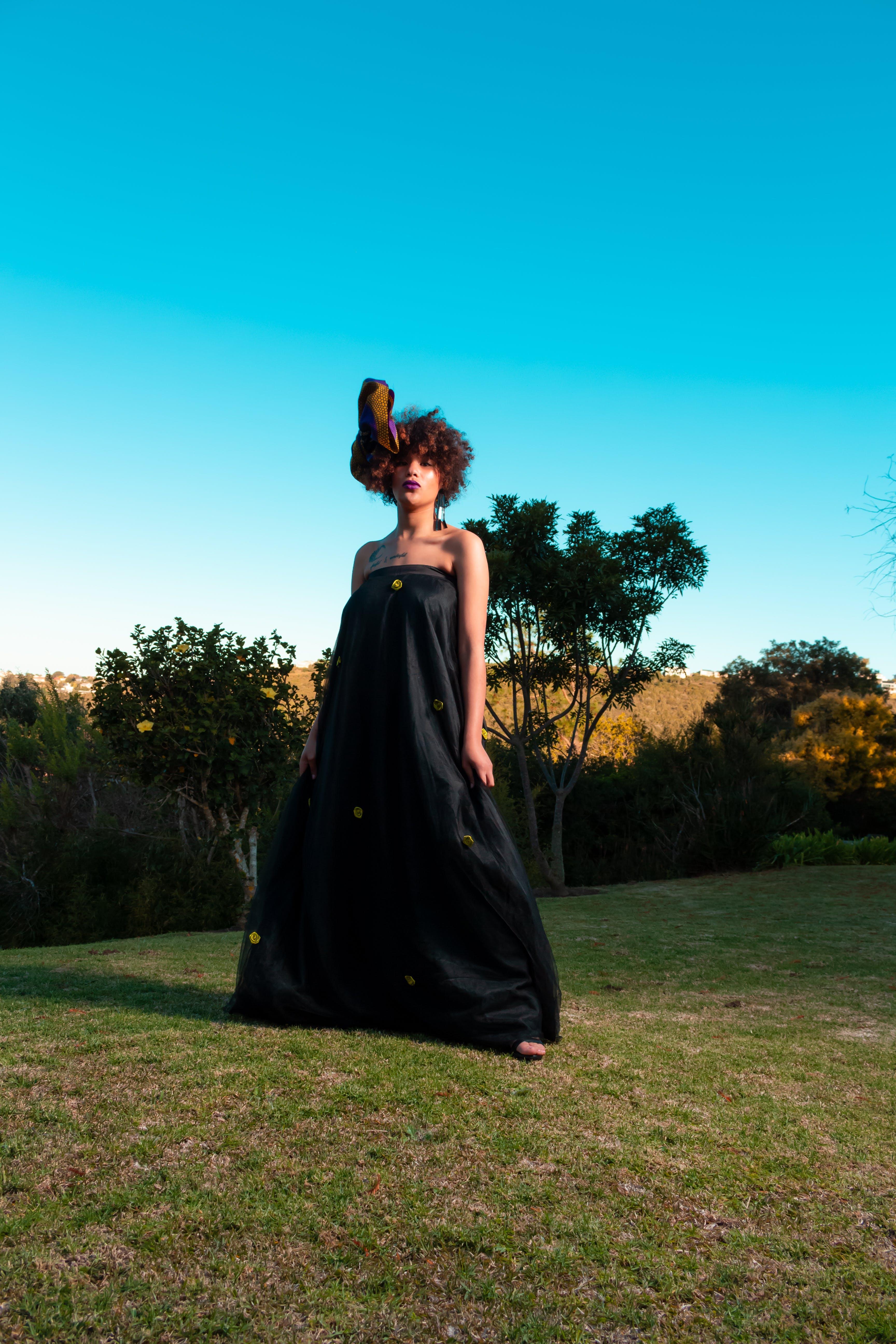 Woman In Black Tube Dress Standing On Green Grass Field