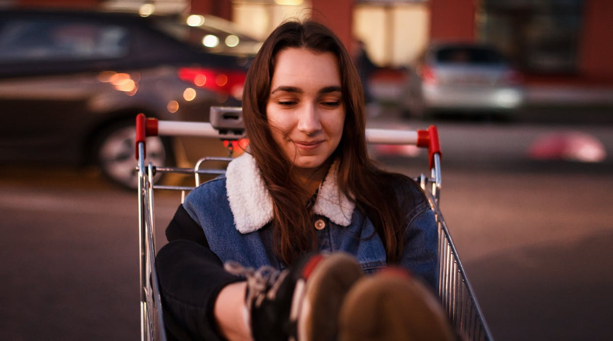 Close-Up Photo of Woman Riding Shopping Cart