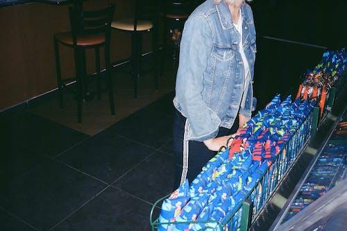 Woman in Blue Denim Jacket Sitting on Chair