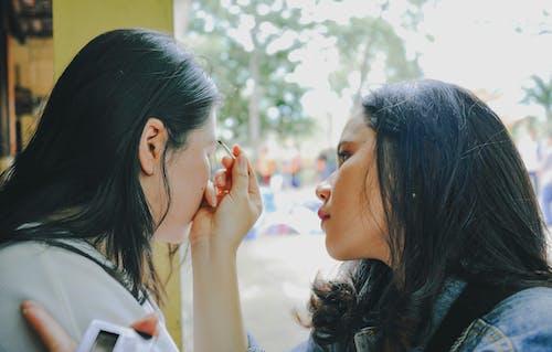 Woman Taking Makeup on Woman Near Window