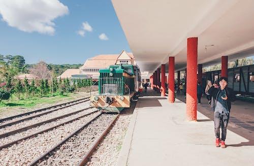 Boy Standing Beside Green Train