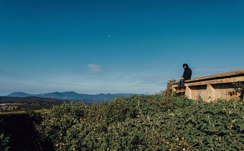 Man Sitting on Concrete Wall Under Blue Sky