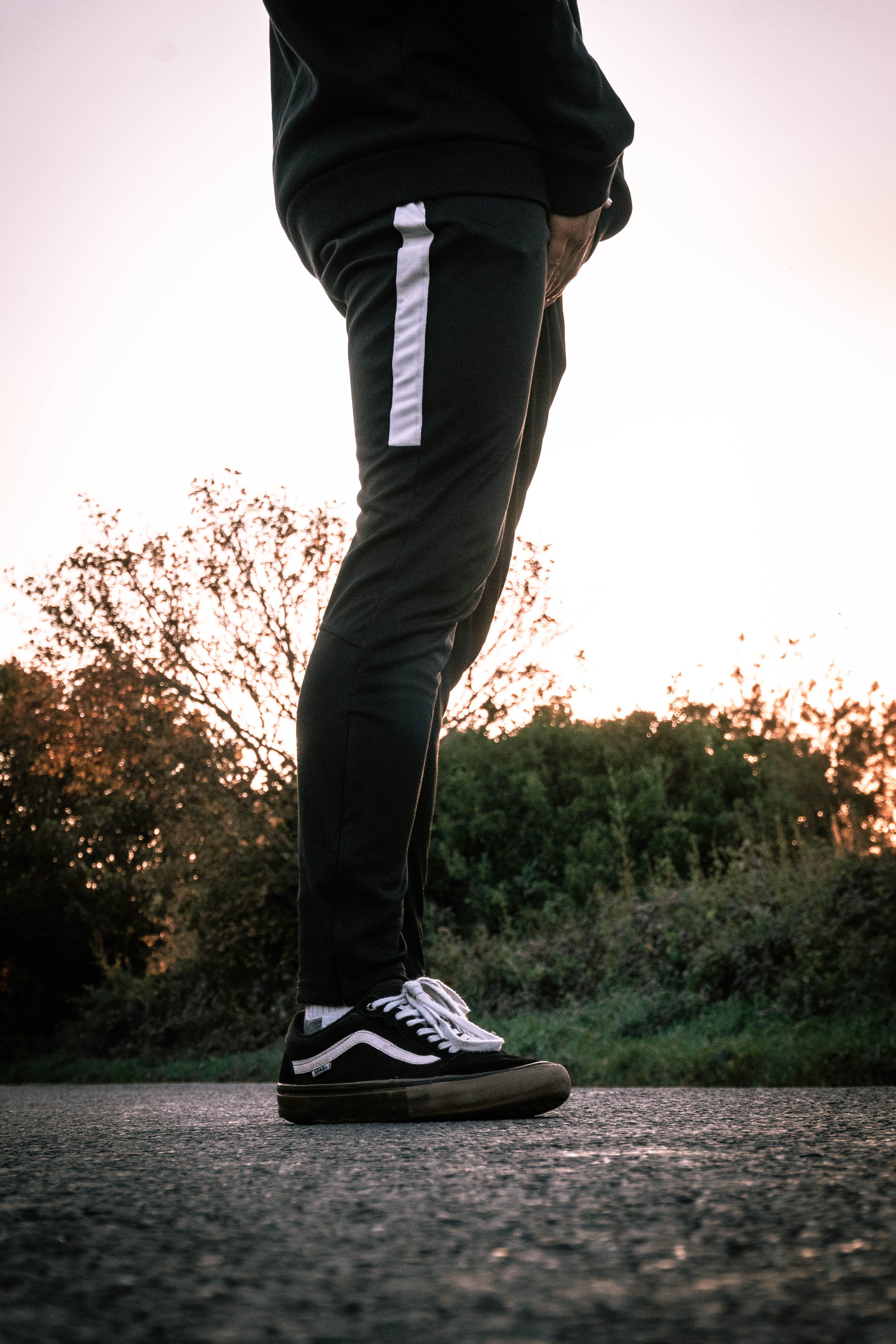 Person Standing on Gray Conrete Road