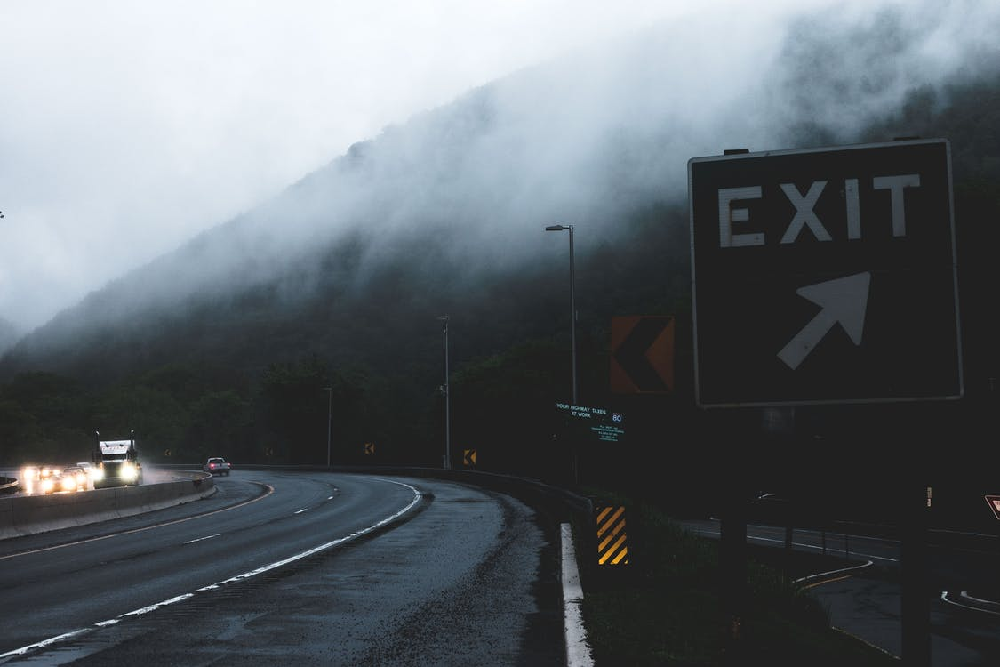 Black and White Exit Signage on Roadside