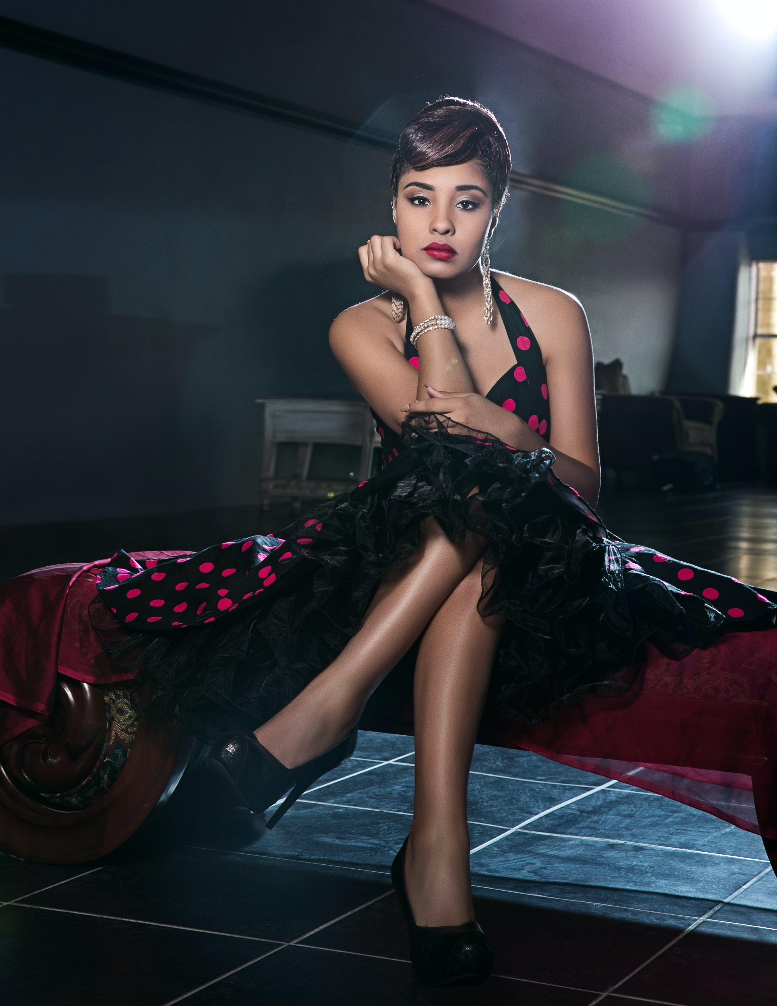 Sitting Woman Wearing Black and Red Polka-dot Halter Dress Inside Dim-lit Room