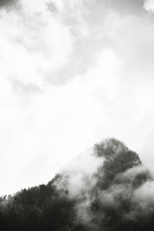 Grayscale Photo of Mountain Peak and Clouds