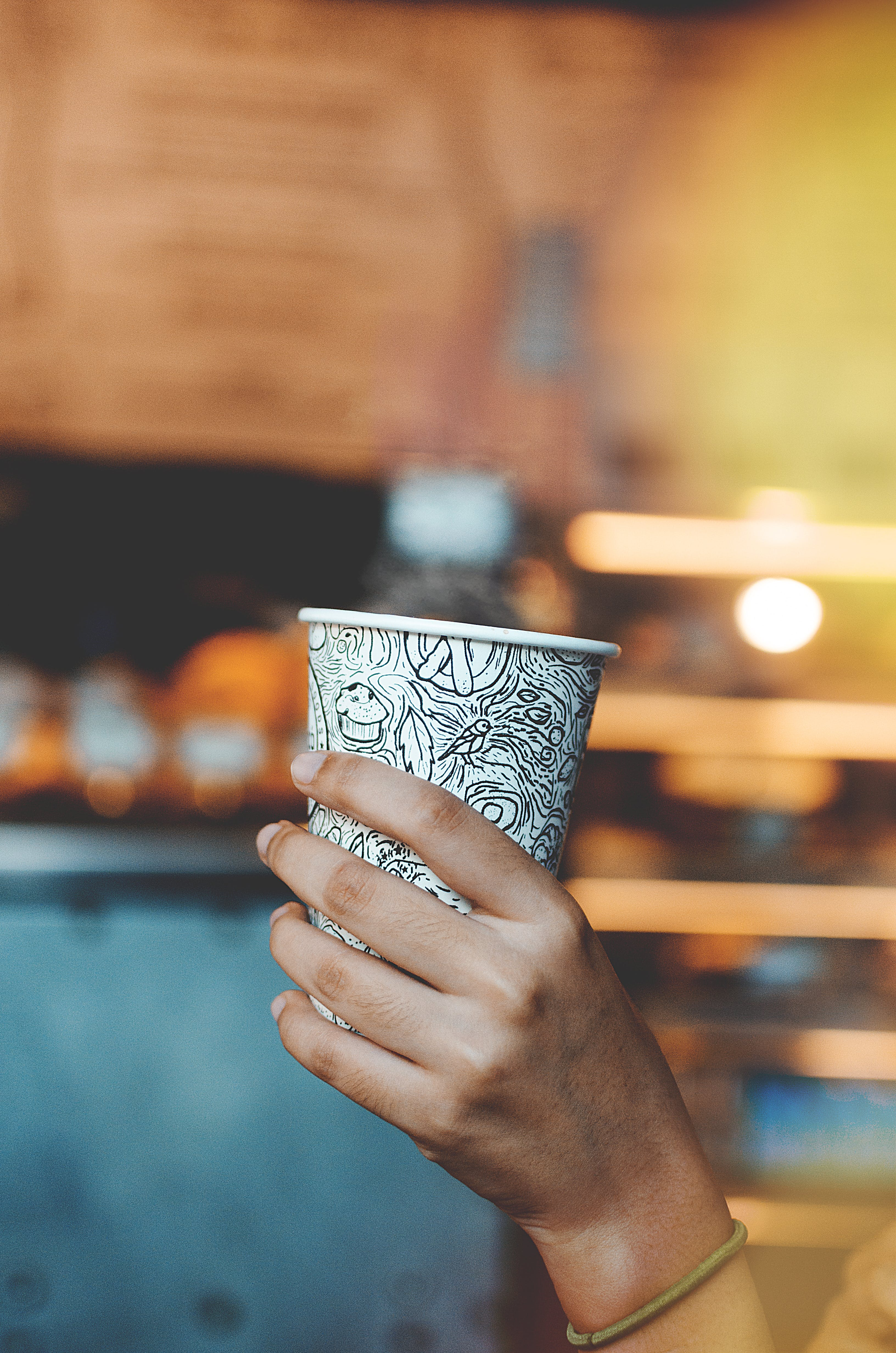 Person Holding White And Black Coffee Cup