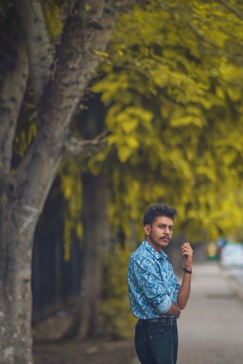 Man Wearing Blue Long-sleeved Shirt Standing Beside Trees