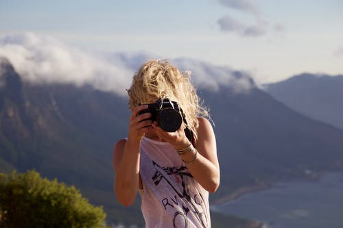 Person Taking Photo With Landscape Background