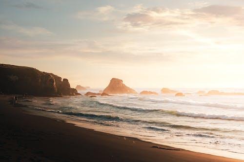 Foamy waves on rocky coast at sunset