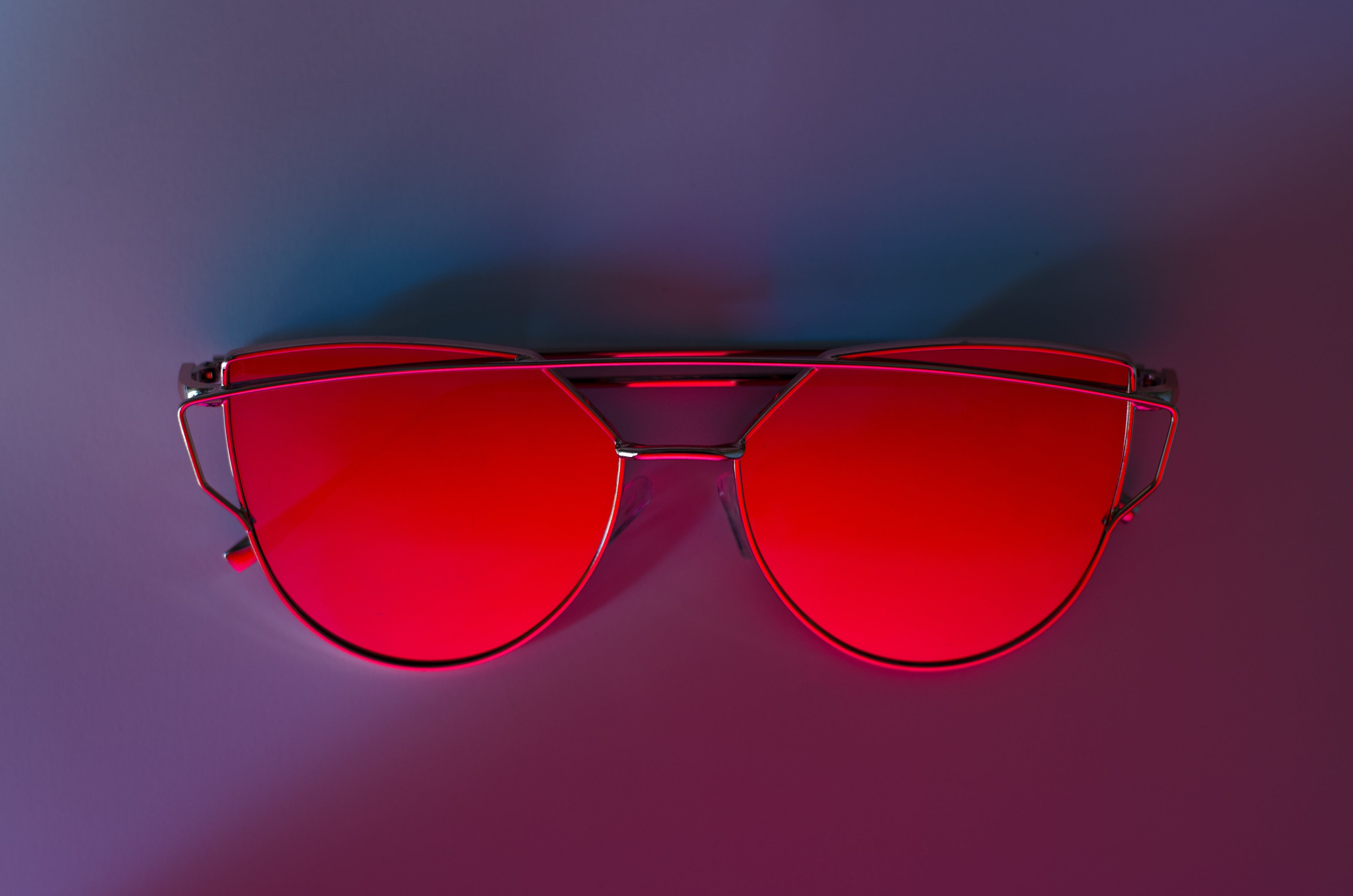 Red Sunglasses on Pink Surface