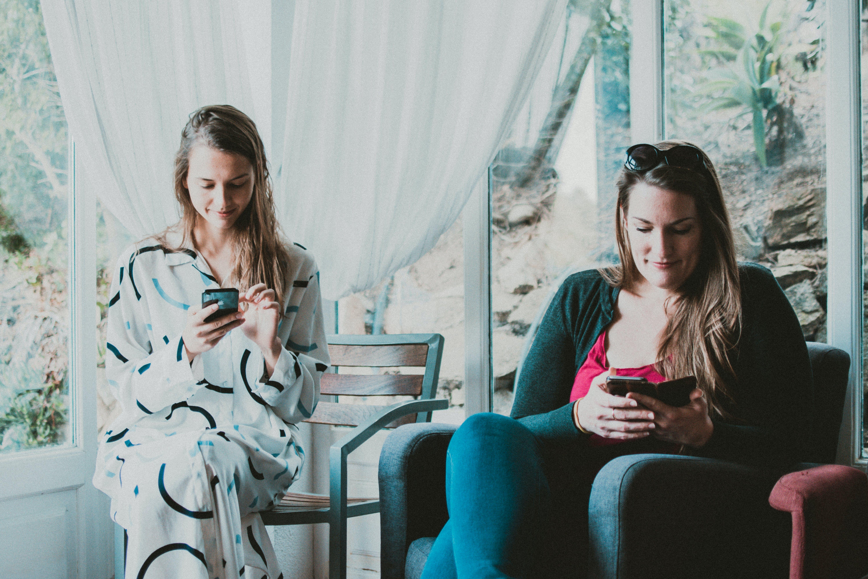 Two Women Using Smartphones Inside Room