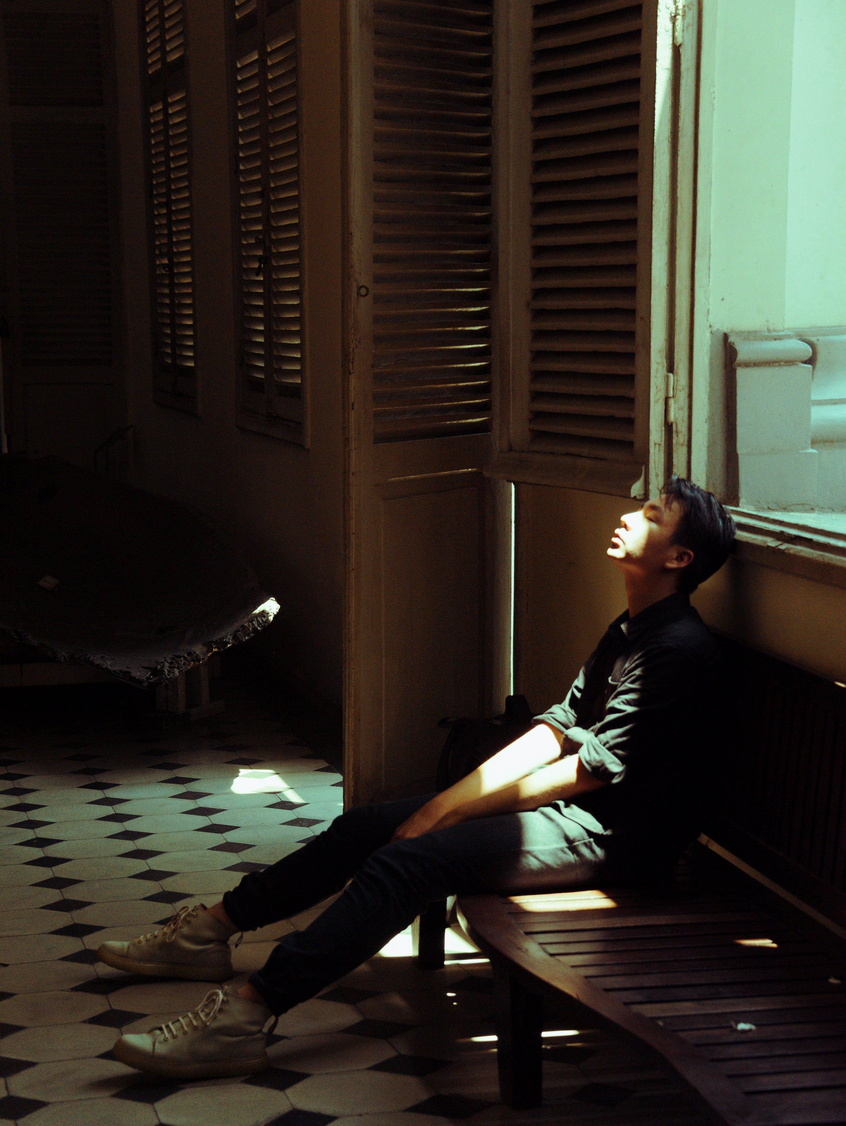 Man in Black Top Sitting on Bench Beside of Door