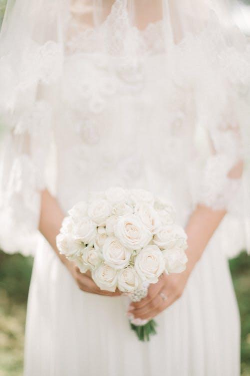 꽃다발을 들고 흰색 웨딩 드레스를 입고 여자