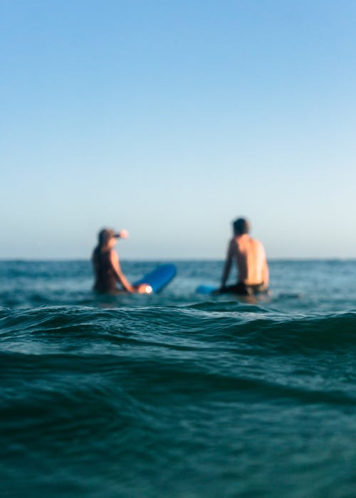 Two Person Riding Blue Bodyboard