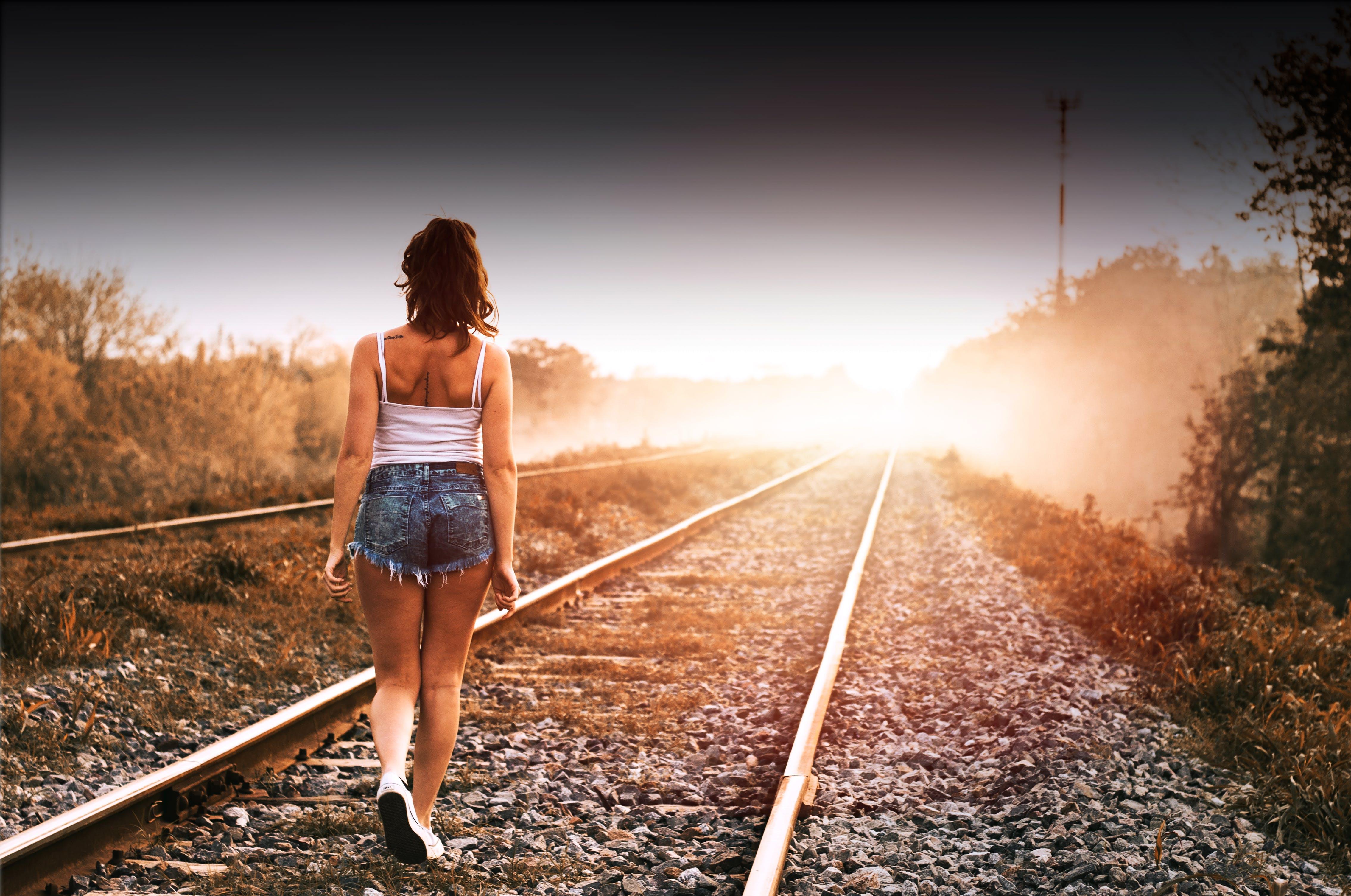 Gratis lagerfoto af gående pige, jernbanelinje, Pige, solnedgang