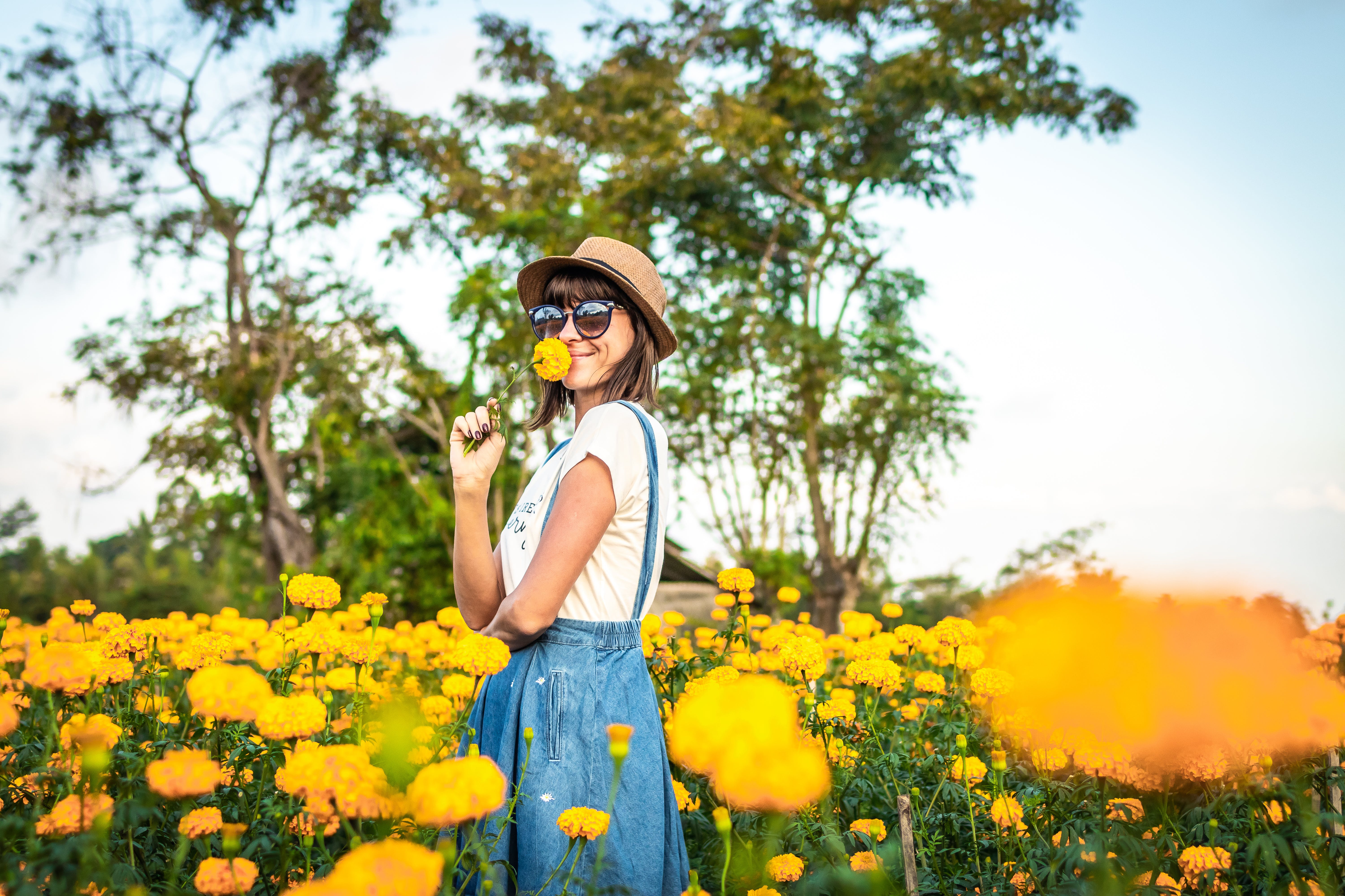 Woman Sniffing Yellow Flowers