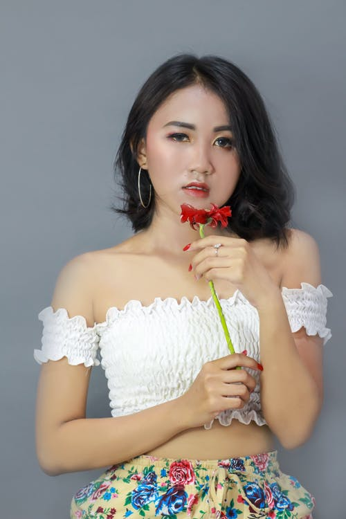 Photo of Woman Holding Red Flower