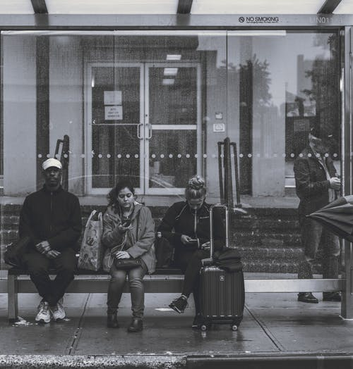 People Sitting on Bench at a Bus Stop