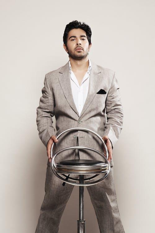 işadamı bir sandalyeyle poz takım elbiseli içeren Ücretsiz stok fotoğraf